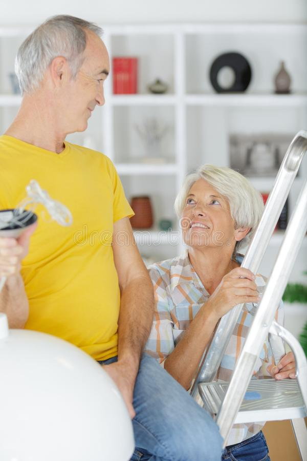 Happy senior couple on ladder royalty free stock photography