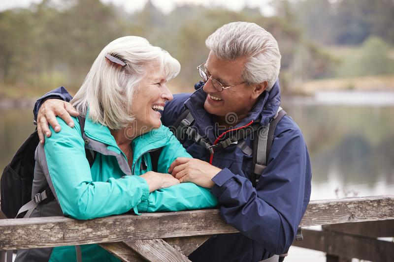 Happy senior couple leaning on a wooden fence smiling to each other, close up, Lake District, UK stock photography