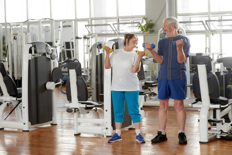 Happy senior couple lifting dumbbells at gym. royalty free stock photos