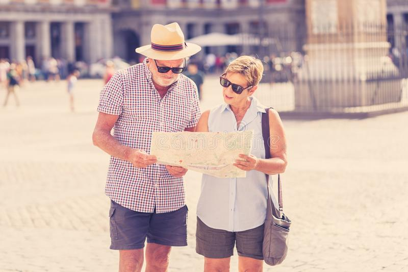 Happy senior couple looking for directions using a map on holidays in a European city. Happy active retired tourist couple searching for their location in Plaza royalty free stock image