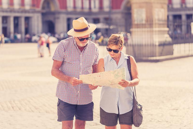 Happy senior couple looking for directions using a map on holidays in a European city. Happy active retired tourist couple searching for their location in Plaza royalty free stock photos