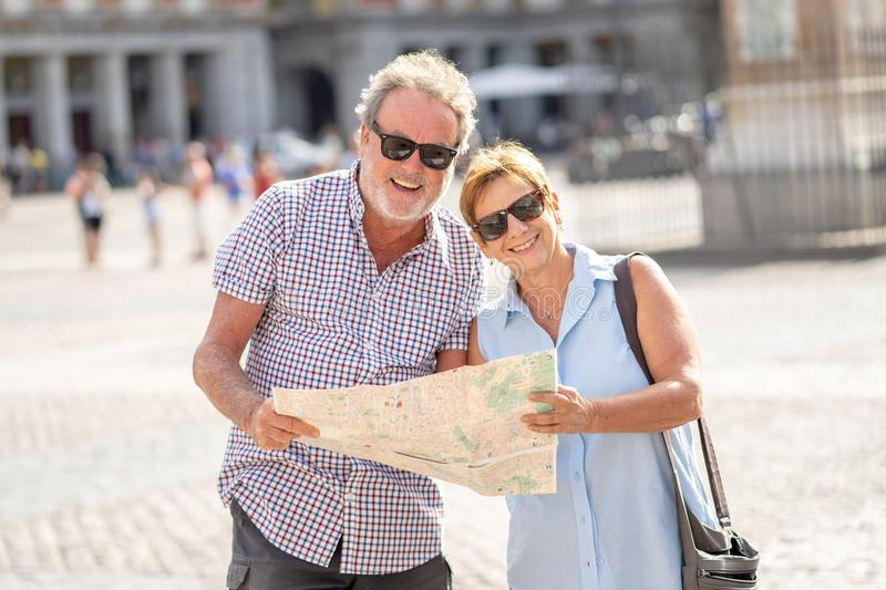 Happy senior couple looking for directions using a map on holidays in a European city. Happy active retired tourist couple searching for their location in Plaza stock images