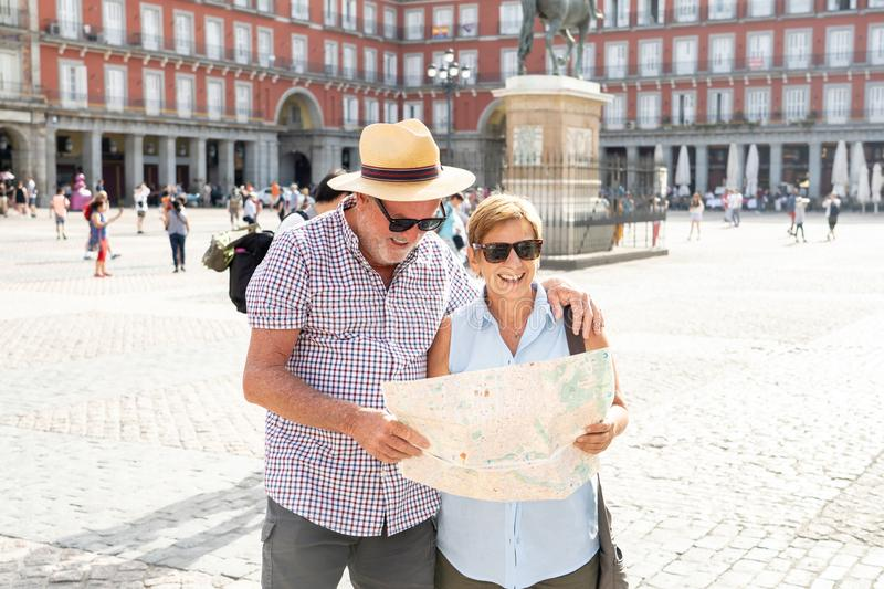 Happy senior couple looking for directions using a map on holidays in a European city. Happy active retired tourist couple searching for their location in Plaza royalty free stock photo