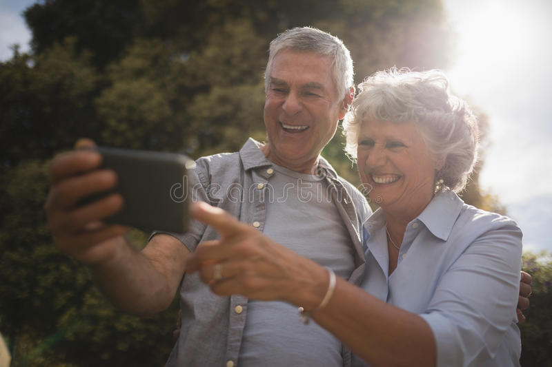 Happy senior couple looking at mobile phone stock photos