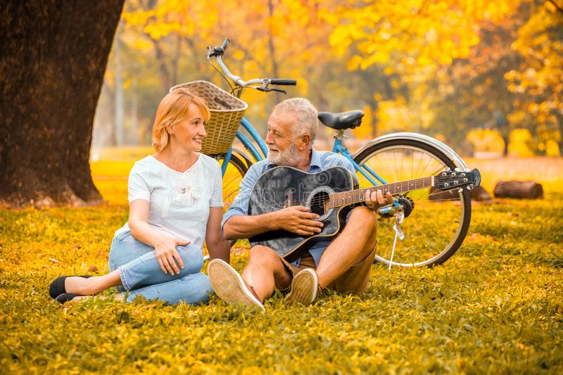Happy senior couple in love playing acoustic guitar in park under big tree with bike in autumn. Senior couple in love playing acoustic guitar in park under big stock photo