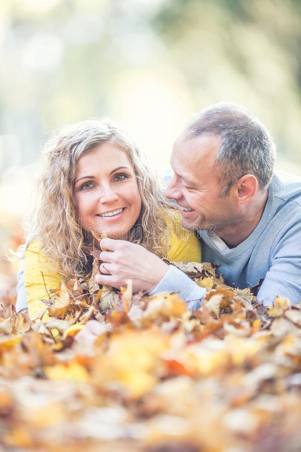 Happy senior couple lying in autumn maple leaves royalty free stock image