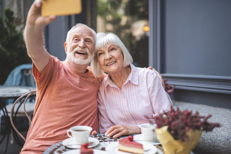 Happy senior couple making selfie in cafe stock photography
