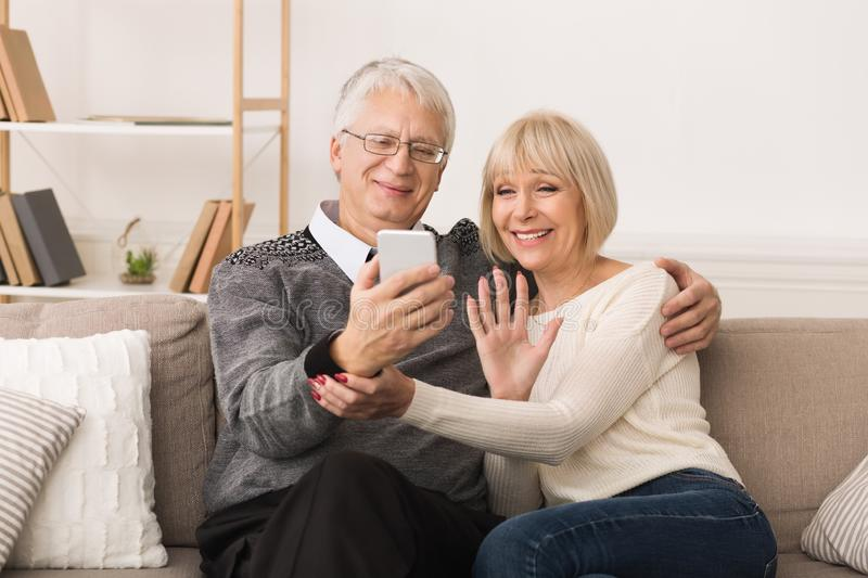 Happy Senior Couple Making Video Call And Waving To Caller stock photos