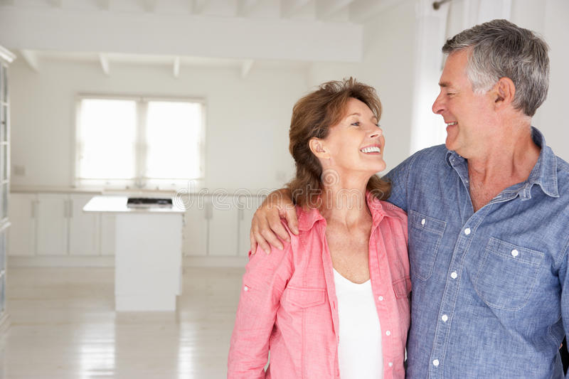 Happy senior couple in new home. Smiling at each other stock photo