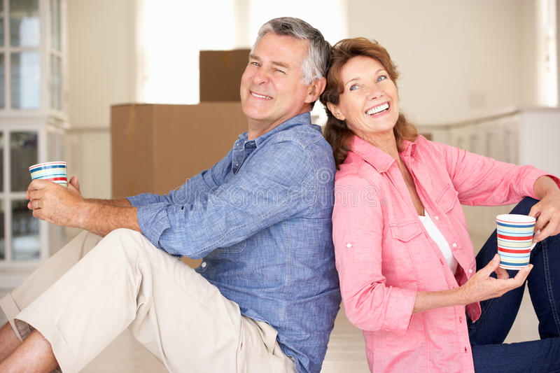 Happy senior couple in new home. Senior couple in new home sat on floor back to back smiling royalty free stock photo