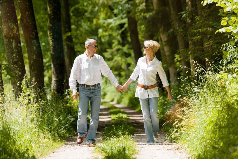 Happy senior couple outdoors running stock photo