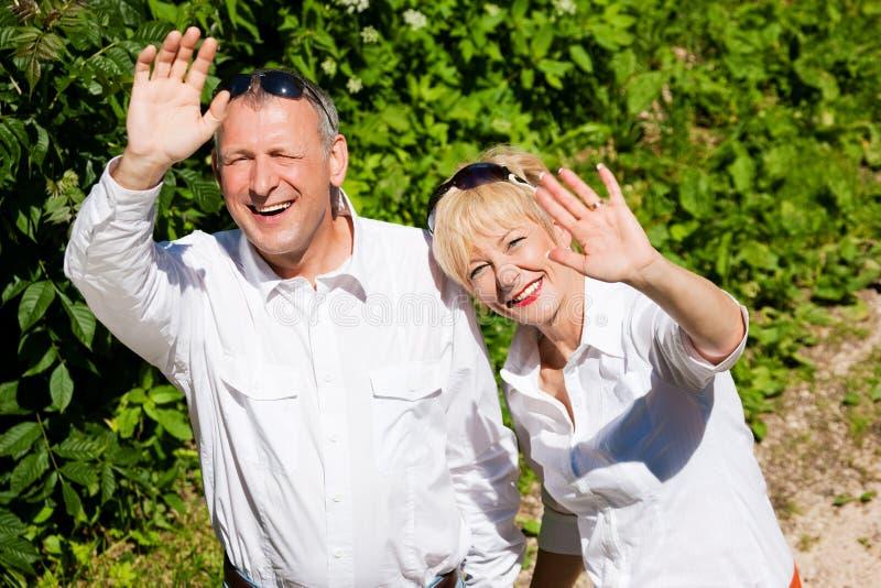 Happy senior couple outdoors waving hands stock image