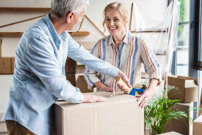 happy senior couple packing cardboard box and smiling each other stock photo