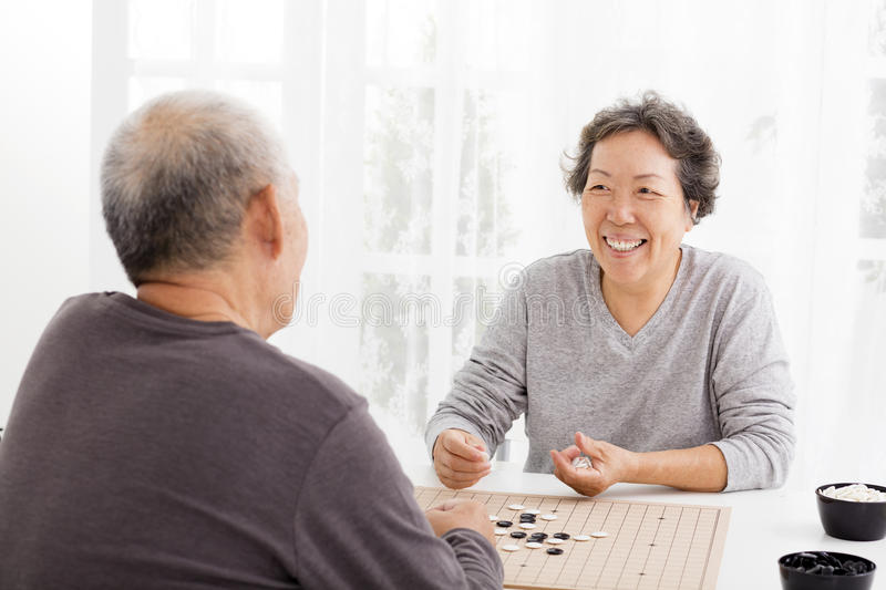 Happy senior couple playing chess in living room stock photography