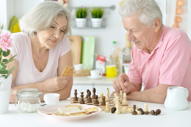 Happy senior couple playing chess royalty free stock photography