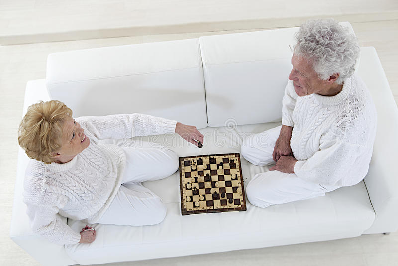 Happy senior couple playing chess royalty free stock photo