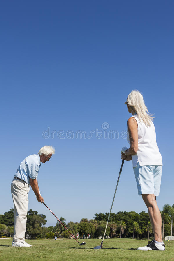 Happy Senior Couple Playing Golf. Happy senior men and women couple together playing golf on a course near a lake they are at the tee driving down the fairway royalty free stock image