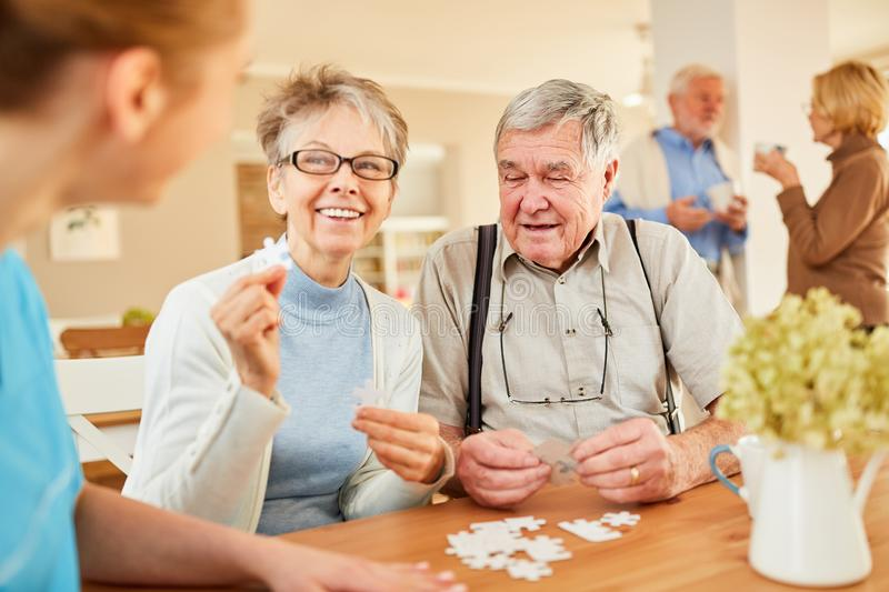 Senior couple playing puzzle in retirement home. Happy senior couple playing puzzle with nursing help at retirement home stock photography