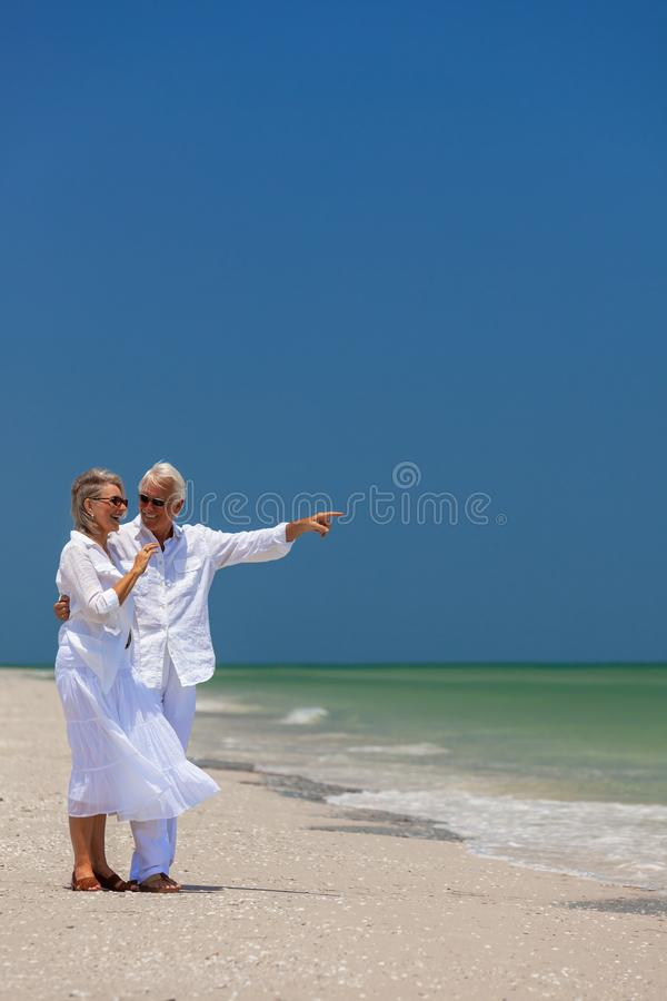Happy Senior Couple Pointing Smiling on Tropical Beach stock images
