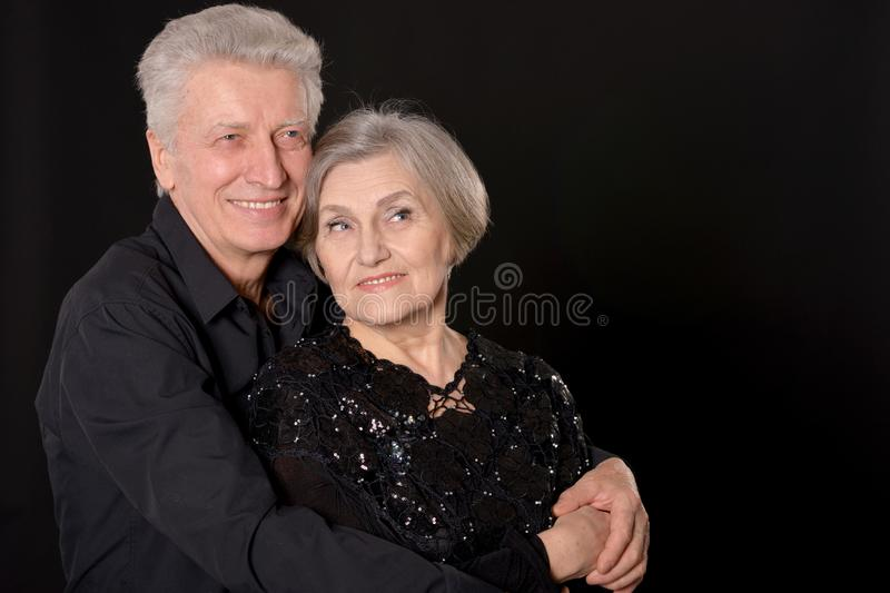 Portrait of happy senior couple posing on black background royalty free stock photo