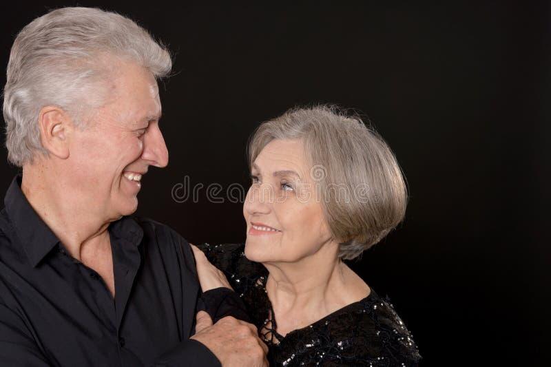 Portrait of happy senior couple posing on black background stock photography