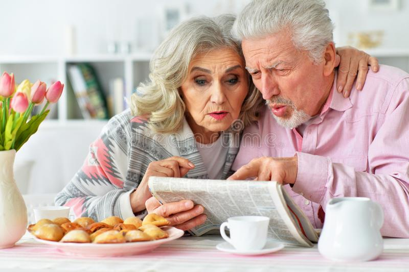 Close up portrait of happy senior couple reading newspaper royalty free stock photography