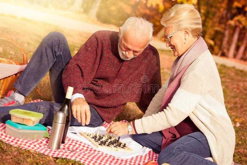 Happy senior couple relaxing in park playing chess together stock images
