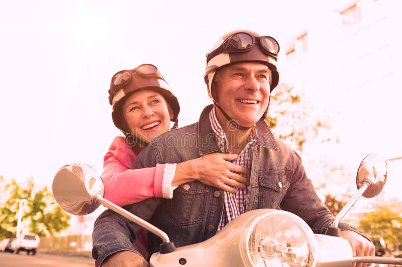 Happy senior couple riding a moped royalty free stock image