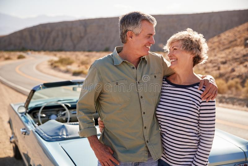 Happy senior couple on road trip standing next to their car royalty free stock photography