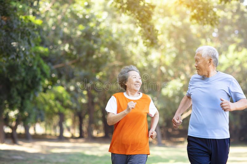Happy Senior couple running in the park stock photography