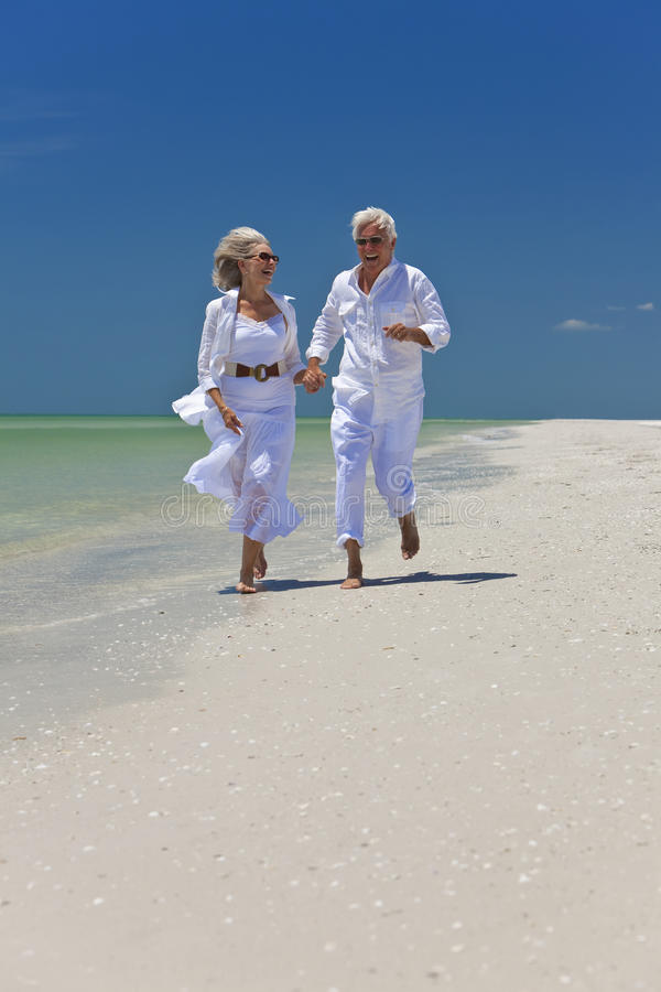 Happy Senior Couple Running on A Tropical Beach stock photography
