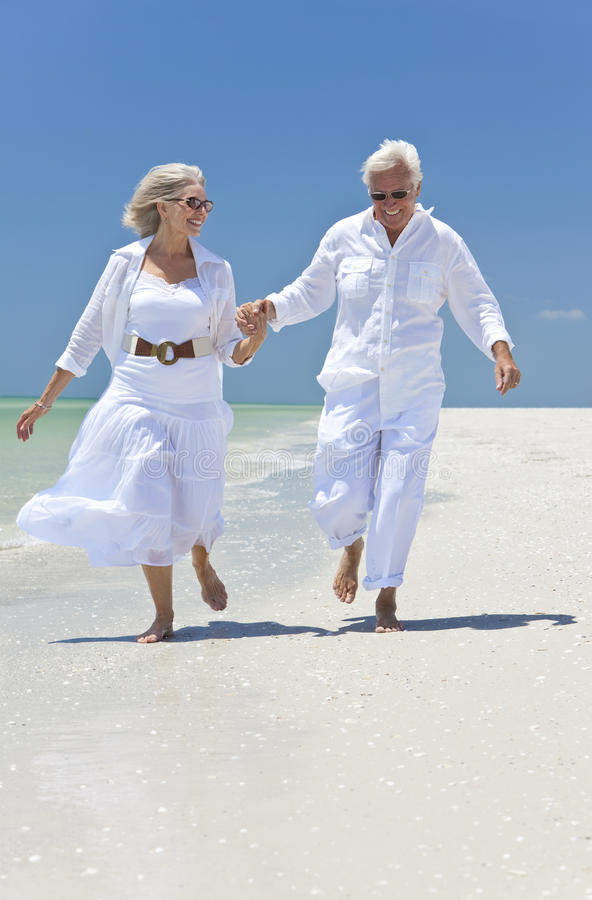 Happy Senior Couple Running on A Tropical Beach stock image