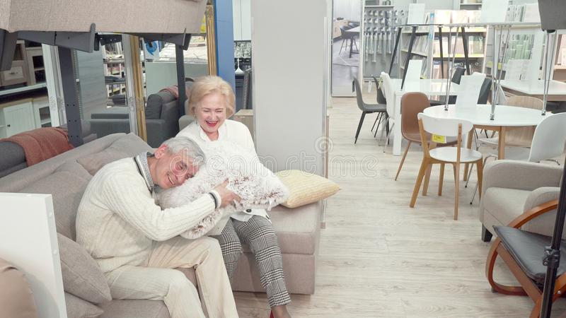 Happy senior couple shopping for furniture and cushions at department store. Lovely elderly cheerful women and her husband sitting on a couch on sale at the royalty free stock image