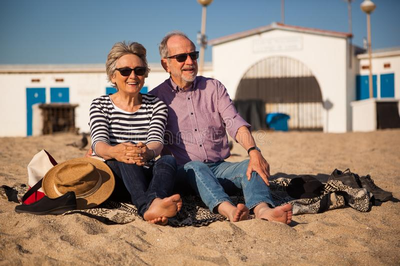 Elderly couple sitting on mediterranean beach, concept happy active seniors. A happy senior couple sitting on the beach and enjoying the view end the sunshine royalty free stock photo