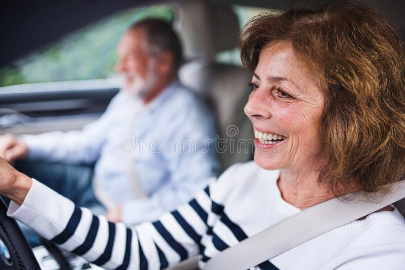 Happy senior couple sitting in car, driving and talking. royalty free stock photo