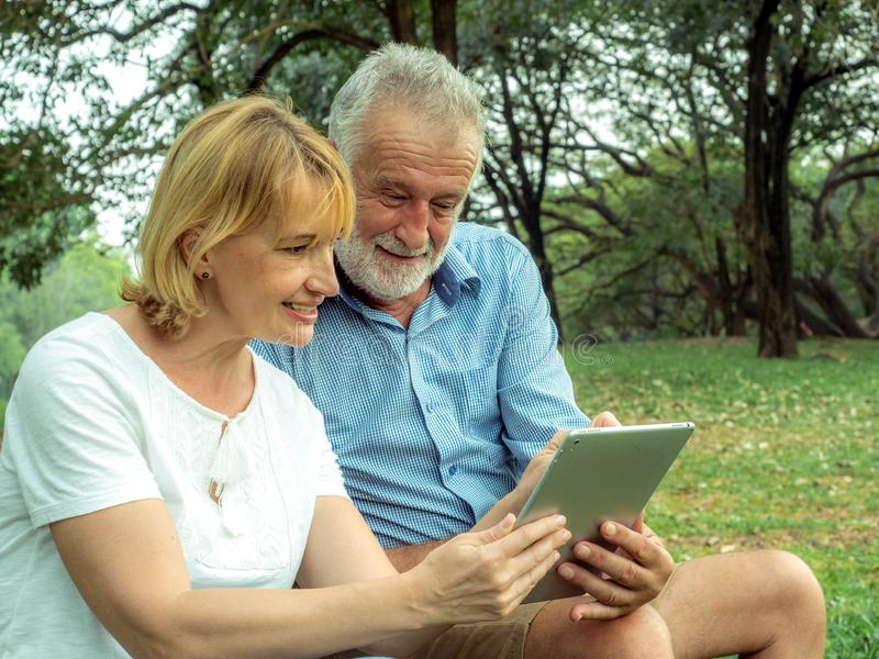 Happy Senior couple sitting on the green grass and enjoying using laptop for online entertainment in the park, Happy life and royalty free stock photo
