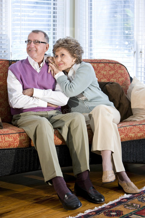 Happy senior couple sitting together on couch. In living room stock photos