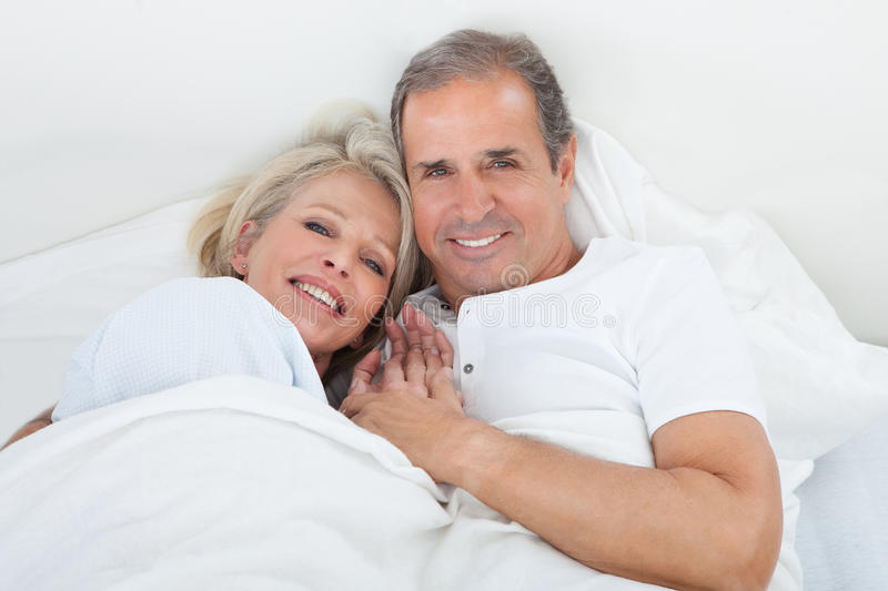 Happy senior couple on sleeping bed royalty free stock images