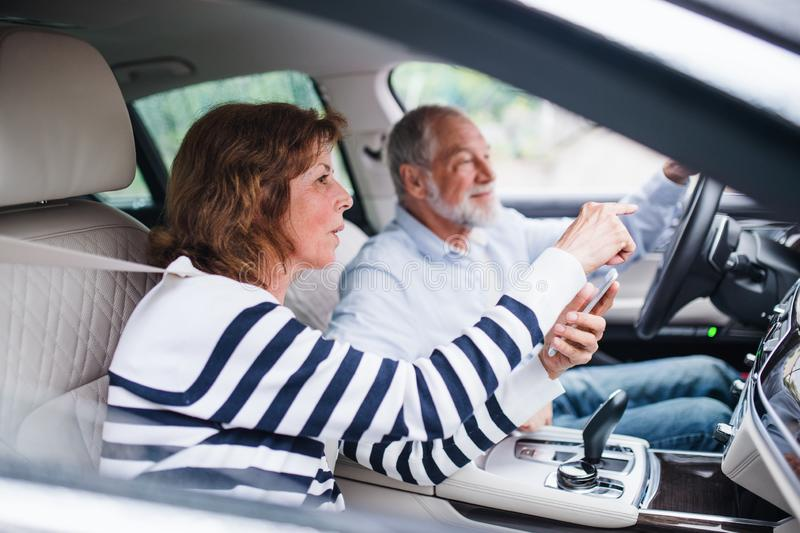 Happy senior couple with smartphone sitting in car, talking. stock photography