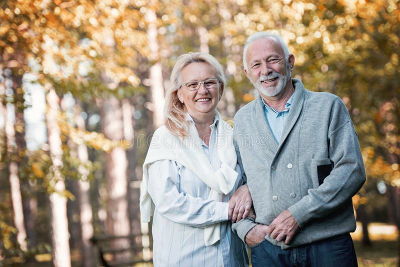 Happy senior couple smiling outdoors in nature royalty free stock photos