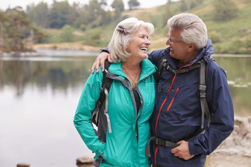 Happy senior couple standing on a shore of a lake smiling at each other, Lake District, UK royalty free stock images