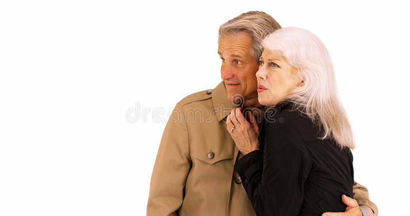 Happy senior couple staying warm and standing in front of white background royalty free stock image
