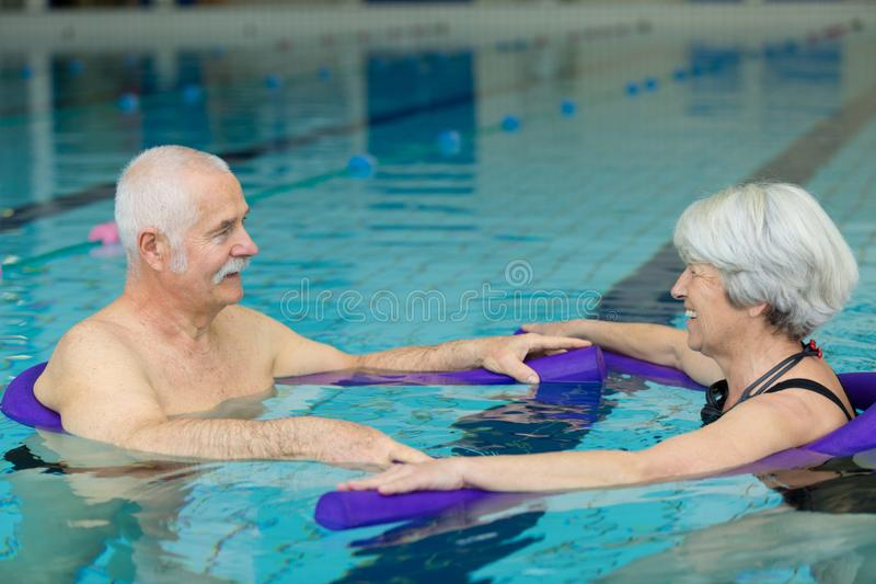 Happy senior couple swimming in pool stock images