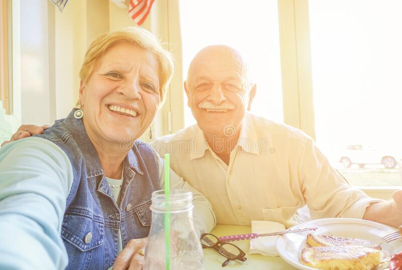 Happy senior couple taking selfie portrait during united states vacation - Mature people enjoying brunch at bar restaurant -. Active elderly and travel concept royalty free stock image