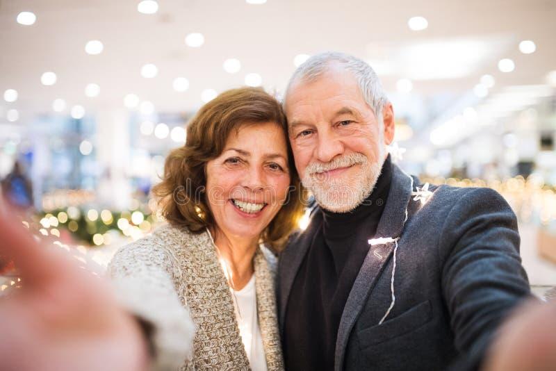 Senior couple taking selfie in shopping center at Christmas time. stock photo