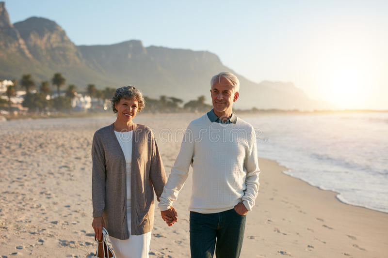Happy senior couple taking a walk on the beach together stock images