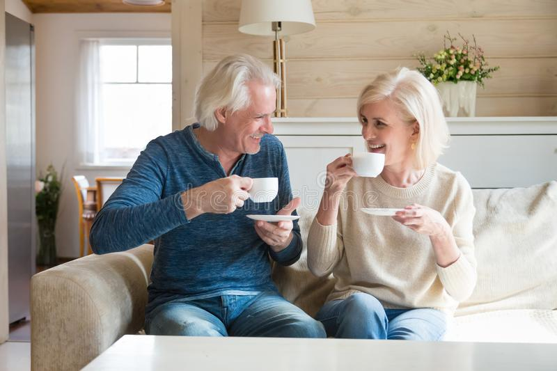 Happy senior couple talking having fun enjoying tea at home stock photo
