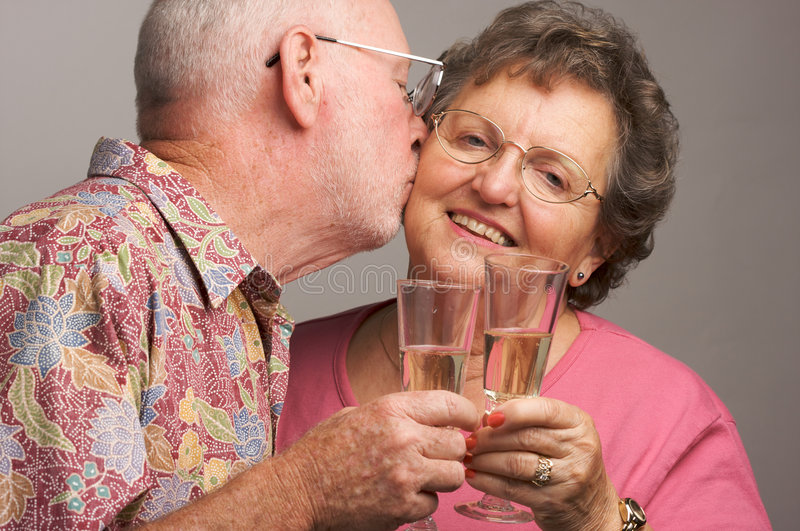 Happy Senior Couple toasting. With Champagne glasses royalty free stock photo