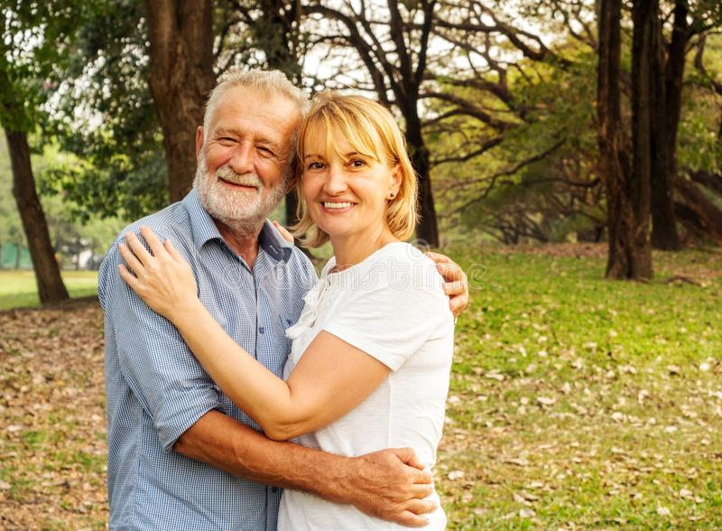 Happy senior couple together in a summer park, Being together and staying strong, happy life stock photo