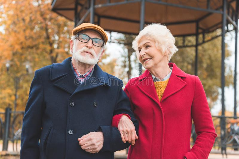 happy senior couple walking in autumn park with gazebo royalty free stock photo